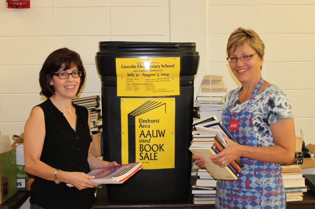 AAUW members Carmen Higgins (left) and Cindy Grau (right) sort books for the annual sale.